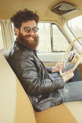 Man with beard driving a retro car