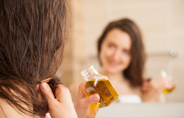 Young woman applying oil mask to hair tips