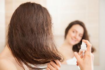 Young woman applying hair spray