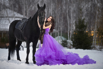Beautiful young woman with a black horse