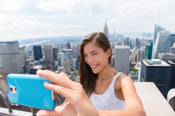 Tourist woman taking mobile phone selfie picture at New York skyline. Asian girl holding blue smartphone for self-portrait photo with view of Manhattan skyscrapers during summer travel vacation.