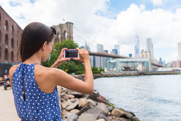 Tourist taking travel picture with phone of Brooklyn bridge and New York City skyline during summer holidays. Unrecognizable female young adult enjoying USA vacations in blue dress.