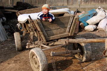Little boy in an old  cart in village countryside