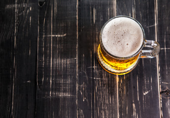 Mug of beer, on a wooden background
