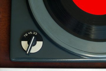 Part of vintage record player with wood finish and vinyl record with red label top view horizontal photo closeup
