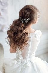 Beautiful young lady bride is looking through the window. Half face. Nice hairstyle. Pastel colors.