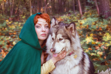 A fairytale fantasy. Red-headed woman in autumn forest. She dressed in renaissance costume. With dog