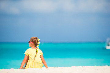 Adorable little girl with frangipani flowers in hairstyle on beach