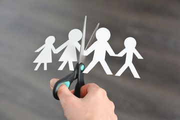 Family divorce concept with human paper shapes and scissors suggesting relationship problems