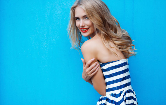 Attractive young woman with long blond hair and gray eyes, dressed in a long white blue stripe dress,makeup and beautiful smile, red lipstick,posing in the summer outdoors on blue background