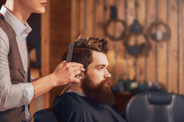 Professional barber styling hair of his client