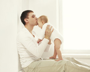 Happy young father kissing baby at home in white room near windo