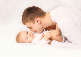 Father and baby at home lying on the bed together bedtime