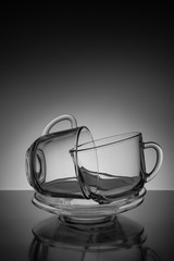 Two glass cup for tea and an empty saucer on a black background