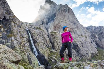 Woman trekker is standing against high mountains waterfall in Ca