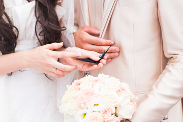 Bride and groom hands holding a small butterfly outdoors