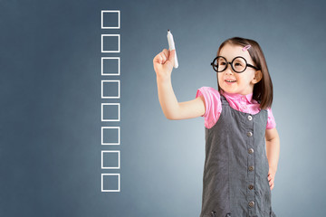 Cute little girl wearing business dress and writing on some blank checklist boxes. Blue background.
