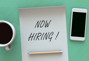 NOW HIRING, message on paper, smart phone and coffee on table