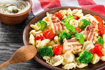 Tortellini with grilled cherry tomatoes, broccoli, red bell pepper, top view
