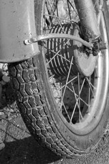 Close up of motorcycle wheel/ Black and white photo. Old vintage card.
