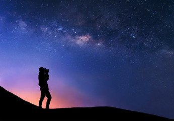 Silhouette of woman is taking the milky way photo on top of mountain before sunrise.