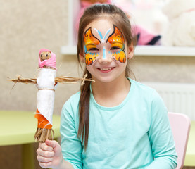 Smiling girl with art make-up with her handmade puppet