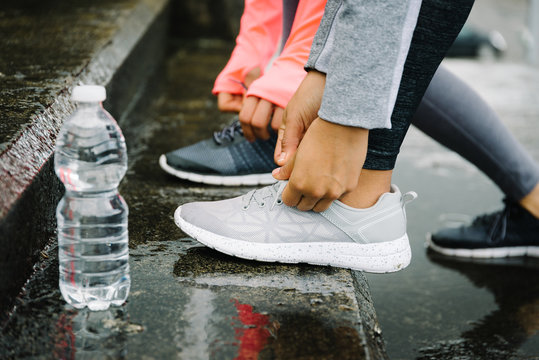 Urban running and fitness workout outdoor under the rain concept. Female athletes lacing sport shoes on wet stairs.