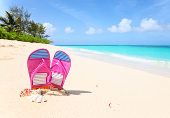 Pink flip-flops  on a sunny beach..Tropical beach vacation concept
