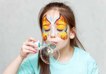 Portrait of cute little girl blowing triple soap bubble