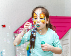 Pretty girl blowing multiple soap bubbles