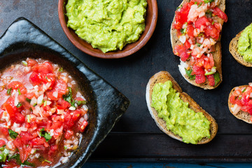 Traditional mexican latinamerican sauce Guacamole, tomato sauce (Salsa), Avocado sandwiches and tomato sandwiches on dark background