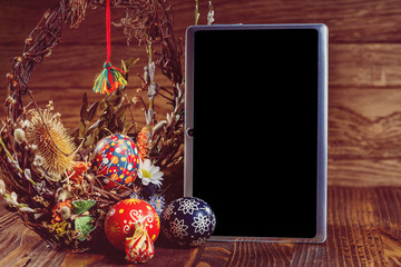 Holiday wreath with colored eggs and tablet pc with blank scree