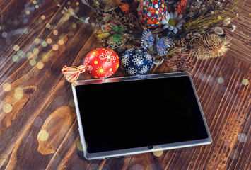 Holiday wreath with colored eggs and tablet pc with blank screen