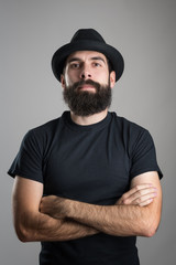Tough confident bearded hipster with crossed arms wearing black t-shirt and hat looking at camera.  Headshot portrait over gray studio background with vignette.