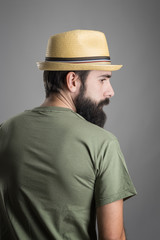 Rear view of young serious bearded man with straw hat looking away. Headshot portrait over gray studio background with vignette.