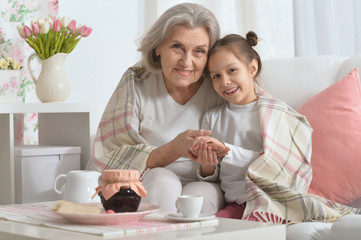 Senior woman with granddaughter with tea