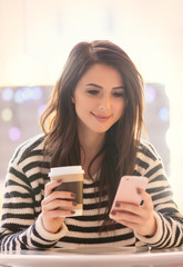 portrait of young woman with cup of coffee and mobile phone