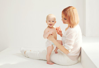 Happy mother playing with baby home in white room