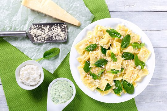 italian ravioli with creamy spinach sauce, top view