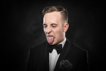 Businessman in suit shows tongue.