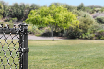 End of a black metal chainlink fence post in a public park