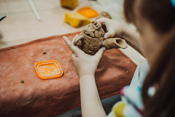 Child sculpts from clay jug