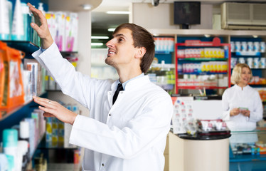 Pharmacist and pharmacy technician posing in drugstore
