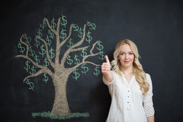 Happy blonde Business woman in front of chalk money tree drawing