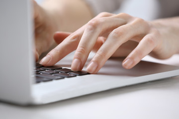 Female hands using laptop on white wooden table, close up