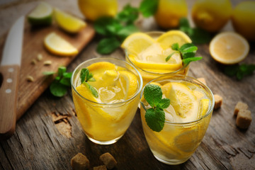 Composition lemonades with lemons and mint on wooden table background