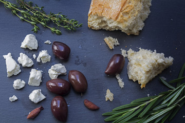 kalamata olives and feta cheese with bread and herbs on a dark slate