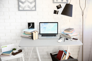 Workplace with laptop, table and lamp in light room