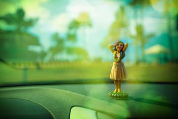 Figur einer Hula Tänzerin für das Auto mit Palmenhintergrund