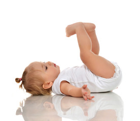 Infant child baby girl in diaper lying on a back and looking up